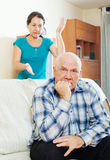 Upset mature man against wife at home Royalty Free Stock Photography