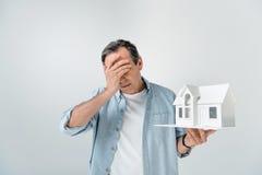 Upset mature man holding house model on grey stock photo