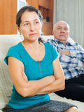 Upset mature woman against elderly husband Stock Image