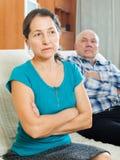 Upset mature woman against elderly husband Stock Image