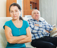Upset mature woman against  husband Stock Images