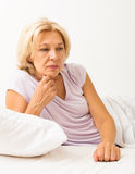 Upset mature woman laying in bed Royalty Free Stock Photography