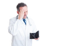 Upset medic or doctor checking empty wallet Royalty Free Stock Image