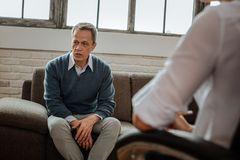 Upset middle-age man sitting on grey couch in cabinet of his doctor. Adult men talking. Upset middle-age men sitting on grey couch in cabinet of his doctor and royalty free stock photos