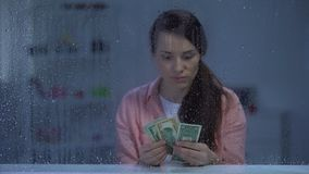 Upset middle-aged woman counting money on rainy day, savings for treatment stock footage