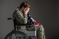 Upset military man feeling helpless. Despondent handicapped veteran sitting in invalid chair. He is covering his face with hands and holding flag. Concept of Stock Photo
