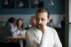 Upset male outcast feel lonely sitting alone in cafe. Upset millennial outsider feel offended lack company, young outcast guy suffer from discrimination, jealous stock images