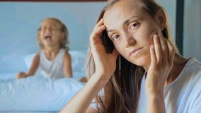 Upset mother with angry little child screaming pillow on the background royalty free stock images