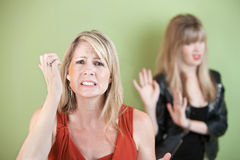 Upset Mother and Daughter. Unhappy mother with frustrated daughter over green background Royalty Free Stock Photo