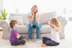 Upset mother looking at children fighting on rug Royalty Free Stock Photos