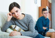Upset mother and son at home. Tired mother and teenage son arguing in domestic interior Stock Image