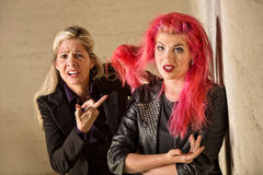 Upset Mother with Teen Hairdo. Upset mother holding teenage girls pink hair Royalty Free Stock Photography