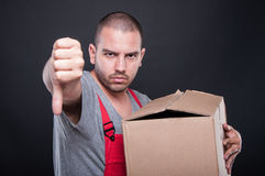 Upset mover man holding box showing thumb down Stock Images