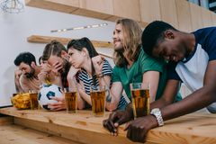 Upset multicultural group of friends sitting at bar counter and watching. Football match stock images