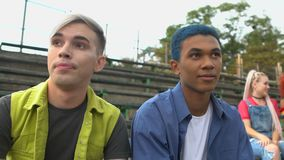 Upset multiethnic male friends listening to young females mocking them, bullying stock video