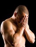 Upset muscular young man over black background Royalty Free Stock Photos