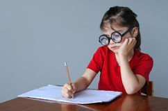 Upset nerdy child doing homework Stock Photos