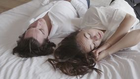 Upset offended girl ignoring boyfriend, turned away, misunderstanding, conflict. Young couple lying in bed close-up. Young couple lying in bed close-up. Girl stock footage