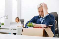 Upset office worker gathering belongings into the box. The worse day ever. Thoughtful depressed aged office worker sitting in the office and gathering his Royalty Free Stock Photos
