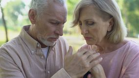 Upset old couple holding hands on walking stick, concept of support, empathy. Stock footage stock footage