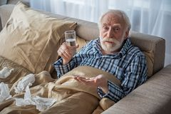 Exhausted senior male taking medicine at home. Upset old man looking at camera with sad look. He is holding pills and glass of water and lying in bed Stock Photo