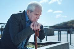 Upset old man thinking about something outdoors stock images