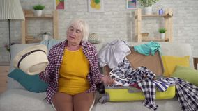 Upset old woman sitting on the couch next to the disassembled suitcase with clothes. Upset elderly woman pensioner sitting on the couch next to the disassembled stock footage