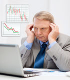Upset older businessman with laptop in office Stock Image