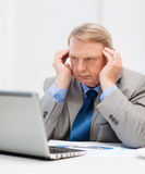 Upset older businessman with laptop in office Royalty Free Stock Photo
