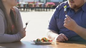 Upset plump man and his pretty girlfriend eating vegetable salad, dieting. Stock footage stock video