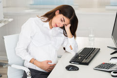 Upset Pregnant Woman Sitting At Computer Desk royalty free stock images