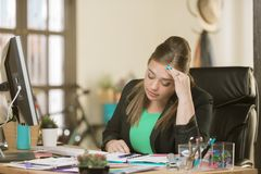 Upset Professional Woman in a Creative Office. Overworked creative professional woman in her office Stock Photo