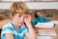 Upset pupil sitting at his desk Stock Photos