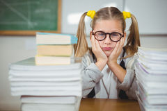 Upset pupil between stack of books on her desk Royalty Free Stock Images