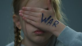 Upset refugee child closing her eyes with palm, war inscription on hand, crisis. Stock footage stock footage