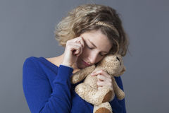 Upset 20s girl cuddling loving comforter to relax herself. Childhood and tenderness concept - sad young blonde woman hugging her teddy bear with tenderness for Stock Image