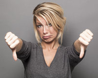 Upset 20s girl expressing frustration with thumbs down Royalty Free Stock Photos