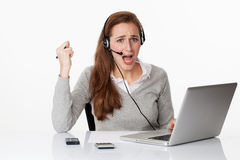 Upset 20s working woman with headset and computer,white office Stock Image