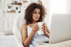 Upset sad beautiful african girl looking at laptop holding cup sitting in chair at home spending her weekend alone. Royalty Free Stock Image
