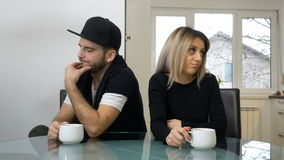 Upset sad couple drinking coffee after a fight sitting in the kitchen stock video