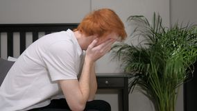 Upset sad redhead man sitting on side of bed. 4k , high quality stock video footage