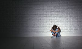 Upset sad sad child girl in stress cries at an empty dark wall. Upset sad sad child girl in stress sits and cries at an empty dark wall Royalty Free Stock Photo