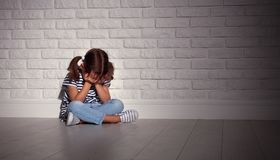 Upset sad sad child girl in stress cries at an empty dark wall. Upset sad sad child girl in stress sits and cries at an empty dark wall Royalty Free Stock Images