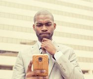 Upset sad skeptical unhappy serious man texting on phone Royalty Free Stock Images