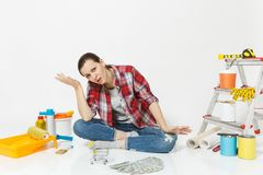 Upset sad woman holds bundle of cash money, supermarket grocery push cart for shopping. Instruments for renovation stock image