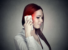 Upset sad woman talking on mobile phone. Cellular mobile radiation concept. Upset unhappy woman talking on mobile phone isolated grey wall background. Cellular Stock Images