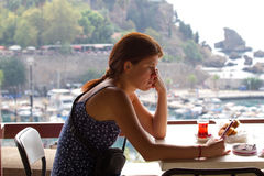 Upset sadness girl sitting in cafe and leafing through a smart phone. Antalya, view old city, landscape Royalty Free Stock Photo