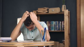 Upset schoolboy doing homework. Teen depression on dark background stock footage