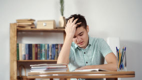 Upset schoolboy doing homework. Teen depression on white background stock images