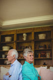 Upset senior couple ignoring each other in living room Royalty Free Stock Images